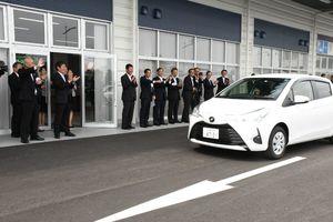 「レンタカーターミナル」のオープン記念イベントで、出席者に見送られながら出発する車両=佐賀市川副町の佐賀空港