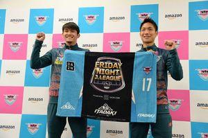開幕戦で来場者に贈られる特製マントを手にする原川力選手(右)と田川亨介選手