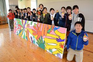 完成した卒業制作と入野小6年の児童たち。中央は冨永ボンドさん=唐津市肥前町の入野小