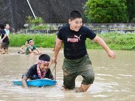 ドロリンピックのそりリレーで、同級生を乗せたそりを懸命に引っ張る児童=有田町の曲川小そばの水田