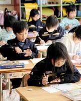 手本を見ながら年賀状を書く児童たち=佐賀市の開成小学校
