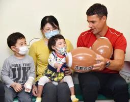 神戸大病院の「こどもセンター」を訪れ、入院患者らと交流する神戸製鋼のダン・カーター選手=24日午前、神戸市