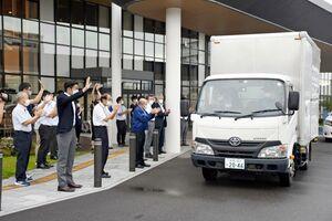 人吉市に届ける段ボール間仕切りを積み込み、小松市長らに見送られて出発するトラック=武雄市役所