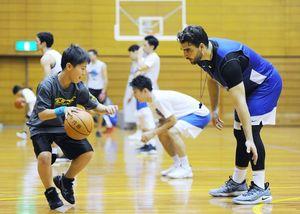 子どもたちにドリブルを教える佐賀バルーナーズのアル・ビェコビッチ選手兼監督=佐賀市の県総合体育館