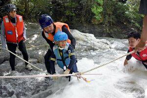 ロープをつたい、流れの速い川を渡る「国際渓流滝登り」の参加者=唐津市七山の滝川川