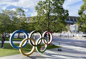 五輪マークのモニュメントと東京五輪・パラリンピックの開閉会式が行われる国立競技場(奥)