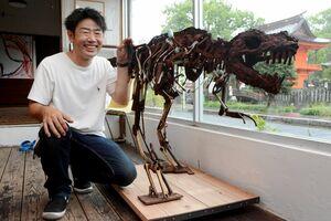 森正彦さんとティラノサウルスの化石をかたどった作品「Re:Bone」=佐賀市の重永デザイン事務所