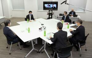 新型コロナウイルス感染症対策の効果を検証する会議の会合で、あいさつする西村経済再生相(左上)、その右は黒川清委員長。奥の画面の右側は京都大の山中伸弥教授=1日午前、東京都千代田区