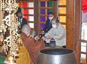 たてた茶を埜口諦順住職(左)に渡す真島美智子さん=吉野ヶ里町の修学院