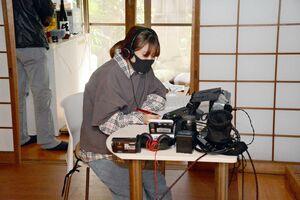モニターをのぞき込む監督の上野咲愛さん=佐賀市松原の松川屋旅館
