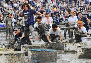 鹿島ガタリンピックの障害物競走で、泥まみれになりながらゴールを目指す参加者=鹿島市の七浦海浜スポーツ公園
