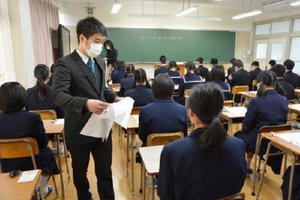 国語の問題と解答用紙を配る試験官=佐賀市の佐賀西高