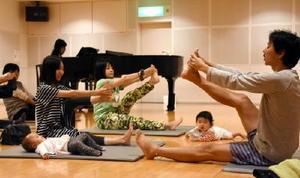 ピアノ演奏が流れる空間で、インストラクターの重松さん(右)に指導されながら体をストレッチする参加者