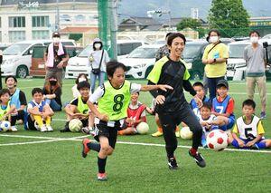 ドリブル対決でボールを追い掛ける岡部将和さん(手前右)と参加者=昨年6月、佐賀市のフットボールパーク佐賀大和