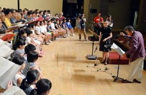 指揮者の小泉和裕さん(右)の指導に、歌声を合わせる市民合唱団=唐津市民会館