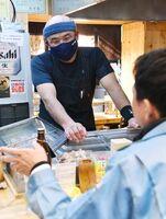 飲食店への時短営業要請が解除された初日、訪れた客と談笑する藤吉大輔さん=8日夜、佐賀市愛敬町の「焼きとり とらさん」