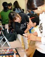 体験者にアドバイスをしながら、丁寧にメークを施していく佐賀女子短大の学生たち=佐賀市の赤松公民館