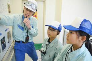 日本製紙の社員から説明を受ける吉居友芽さん(右)と石橋玄基君=熊本県八代市の日本製紙八代工場