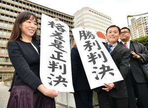 日本郵便の待遇格差を巡る訴訟の判決で、「勝利判決」と書かれた紙を掲げる原告の男性ら=21日午後、大阪地裁前