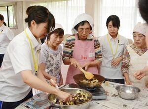 協力してナスを炒める学生と利用者ら=吉野ヶ里町の三田川健康福祉センター「ふれあい館」
