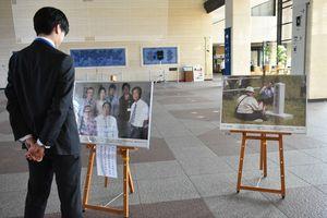 現地での交流を撮影した写真を見つめる来館者=佐賀市の県庁