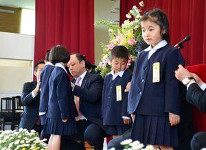 保険会社の支社長などからワッペンを付けてもらう新1年生=佐賀市川副町の西川副小学校