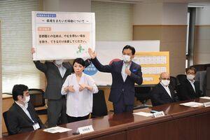 首都圏との往来をできるだけ自粛するように求めた山口祥義知事(中央)=21日午後、佐賀県庁