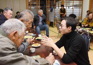 お年寄りとの会話を弾ませる佐賀大経済学部3年の桂飛龍さん=佐賀市川副町の西古賀公民館