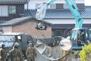 重機でつり上げられるAH64D戦闘ヘリコプターのトランスミッション(中央)=8日午前10時15分、神埼市千代田町
