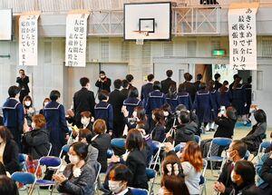 在校生や来賓がいないながらも保護者からの温かい拍手の中、掲げられたメッセージを見ながら退場する卒業生たち=佐賀市の城西中