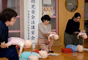 気道内の異物を除去する方法を実践する参加者たち=吉野ヶ里町の三田川児童館