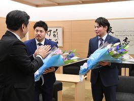 山口祥義知事(左)から花束を受け取る宮崎敏郎選手(中央)と濵口遥大選手=県庁