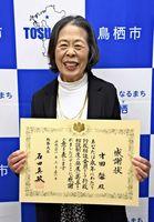総務大臣からの感謝状を手に笑顔の才田馨さん=鳥栖市役所