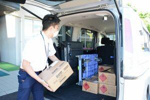佐賀県が配布した消毒液を車に積み込む佐賀市職員=佐賀市八戸の佐賀土木事務所