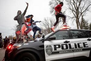 11日、米ミネソタ州の射殺事件の現場付近で、警察車両に上がる人々(スター・トリビューン紙提供、AP=共同)