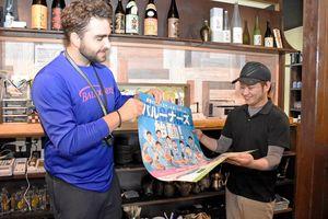 ホーム戦のポスターを手渡す佐賀バルーナーズのアル・ビェコビッチ監督兼選手=佐賀市の飲食店「元屋」