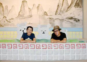 『パンダ銭湯』を再現したコーナーで撮影に応じる亀山達矢さん(右)と中川敦子さん=久留米市美術館