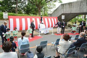 諸井謙司さんが制作した少女像の除幕を行う関係者ら=佐賀市の佐賀県立図書館