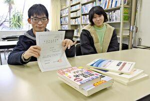 登録販売者試験の合格通知を手にする宮﨑大義さん(左)と池田真弥さん=唐津市の唐津ビジネスカレッジ