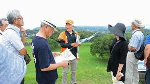 天守台で、旅行客に離島と韓国の位置関係について説明する前田さん=唐津市鎮西町の名護屋城跡