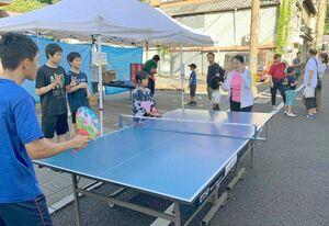 温泉卓球大会の来場者とうちわで対戦する卓球部員(手前)(提供)