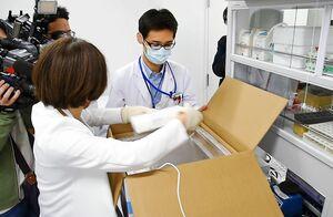 搬入された新型コロナウイルスのワクチンを取り出す担当者=5日午前、佐賀市の佐賀大医学部附属病院