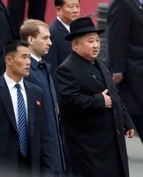 ロシアのプーチン大統領との首脳会談に臨むため、ウラジオストク駅に到着した北朝鮮の金正恩朝鮮労働党委員長(右)=24日(共同)