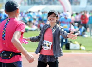 ゴール付近でランナーを応援する大会ゲストの湯田友美さん=佐賀市の県総合運動場陸上競技場