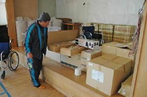 「なんじゃろか」と言って備蓄品の箱をのぞく区長の樋口洋二さん。避難所運営について唐津市からの説明が十分に行き届いていない=1月6日、向島の入野小向島分校
