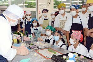生徒の前で和菓子づくりを実演する「ものづくりマイスター」の古河義継さん(左)=佐賀市の佐賀商高