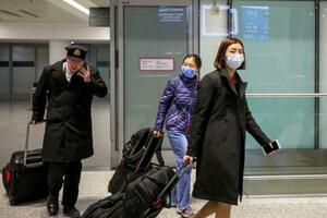 カナダのトロントの空港にマスク姿で到着した人たち=25日(ロイター=共同)