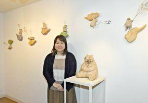 2年ぶりの個展を開いている小泉夕可利さん。新作の「しろくま如来座像」(右)や「雲中しろくま菩薩」などを並べる=佐賀市のギャラリーシルクロ