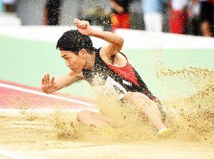 【陸上】男子三段跳び 砂をまき散らして着地する佐賀工の坂井柚輝=24日、佐賀市のSAGAサンライズパーク陸上競技場