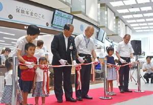 1階窓口の改築を祝い、テープカットを行う秀島市長(右から3人目)ら=佐賀市役所